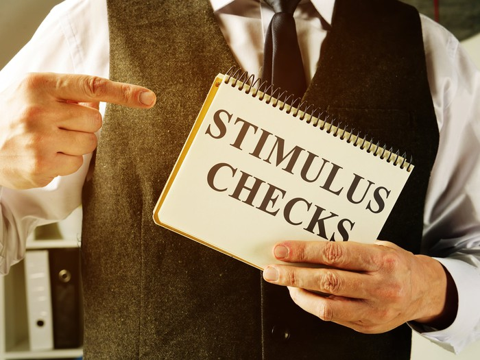 Person holding a sign that reads stimulus checks.