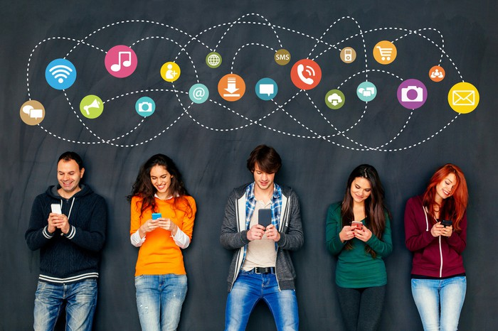 A group of young people interacting with smartphones, while various icons (i.e. camera, email, shopping cart) are displayed above their heads.