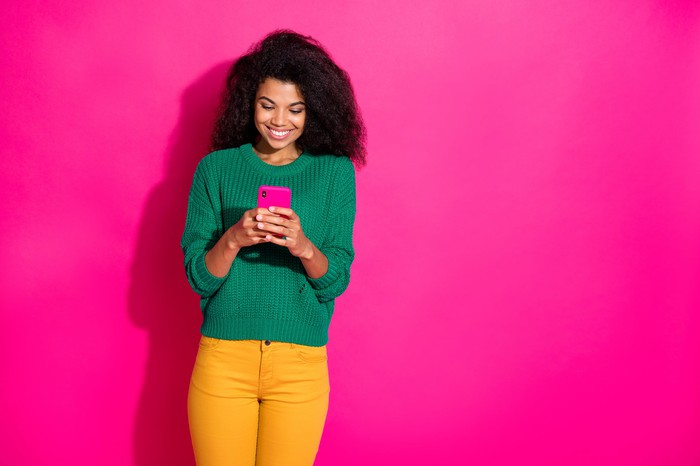 Smiling woman interacting with smartphone.