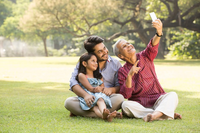 A 3-generation family taking a selfie together in a park.