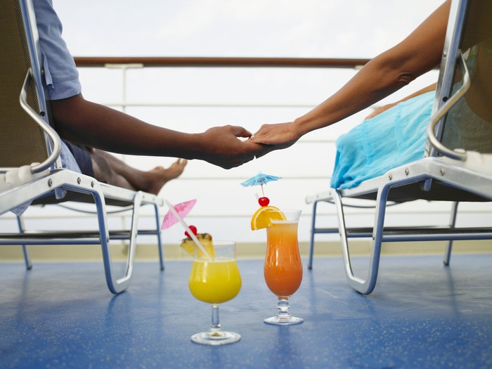 A couple holding hands on a cruise ship with umbrella drinks on the floor.