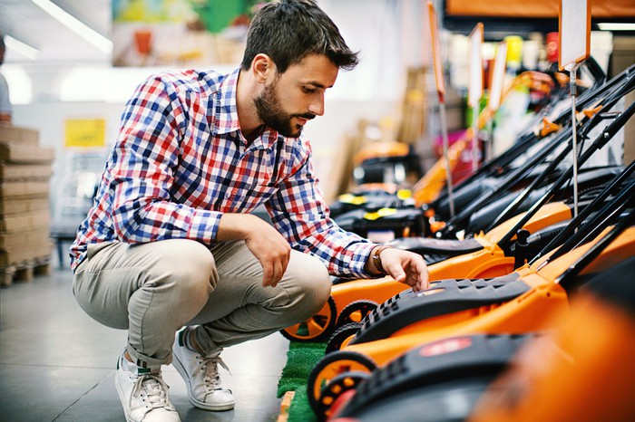 A man looking at a lawnmower.