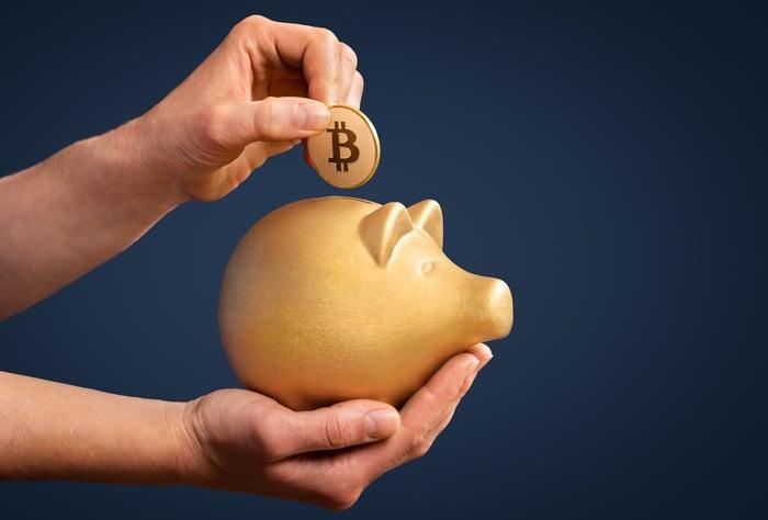 Someone putting a coin with the Bitcoin logo into a golden piggy bank.