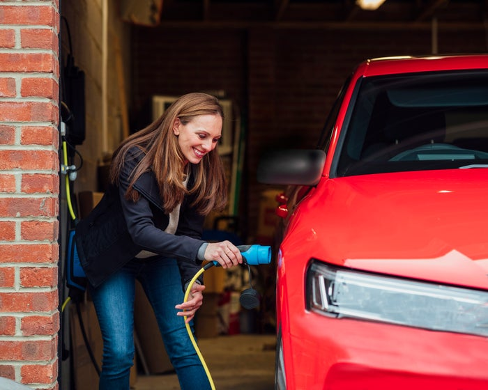 A happy person plugs their red car in to charge.
