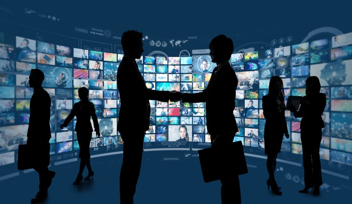 Two businessmen shaking hands in silhouette in fornt of dozens of TV screens.