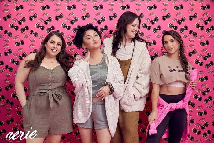 Four young women wearing loungewear pose in front of a pink background.