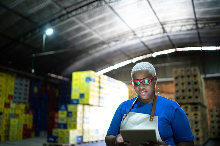 A worker uses technology in a warehouse.