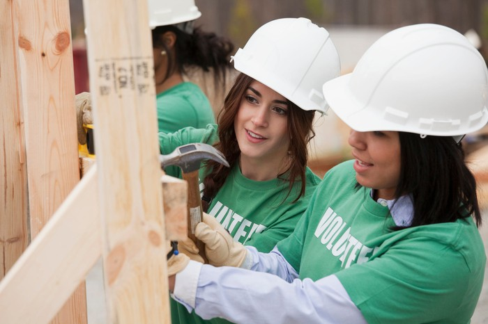 Three women in hard hats constructing a house at a job site.