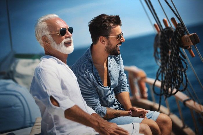 A couple wearing sunglasses enjoying themselves on a sailboat.
