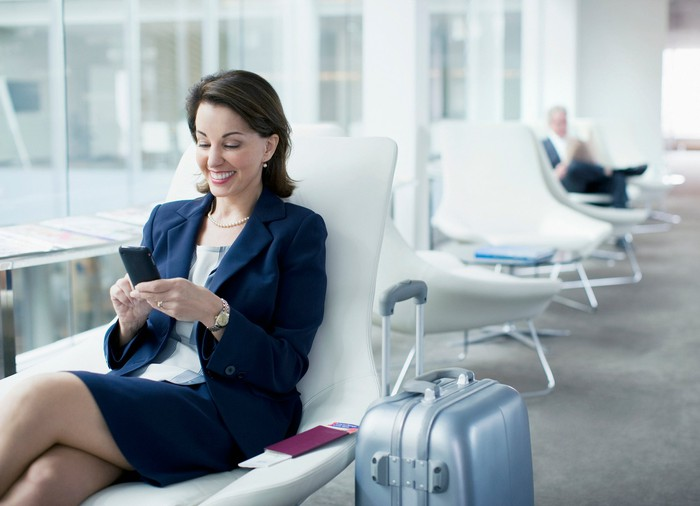 A woman waiting in an airport, looking at her phone, smiling.
