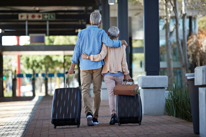 Retired couple going on vacation with luggage.