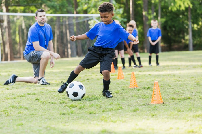 Youth soccer team with boy dribbling soccer ball while coach looks on.