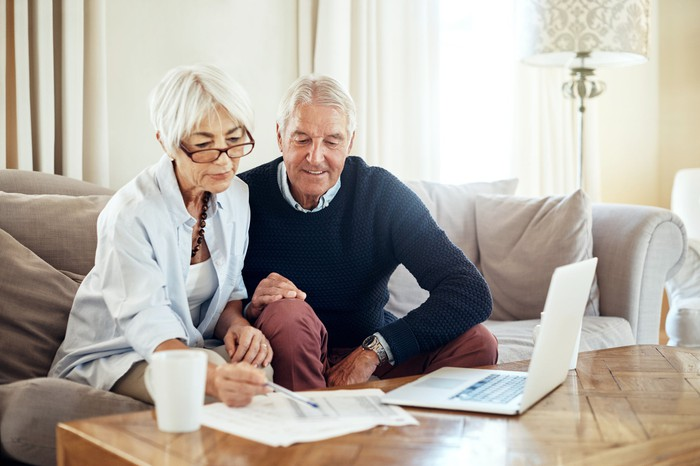 Two elderly people looking over finances in front of a computer sitting on a coffee table.