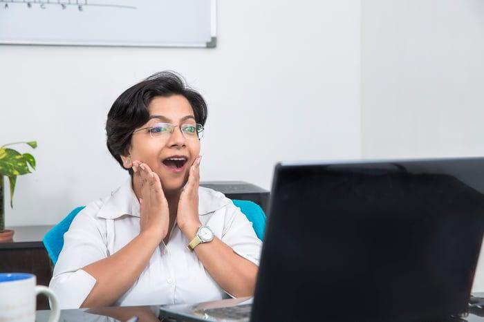 Une femme est contente de ce qu'elle voit sur un écran d'ordinateur.