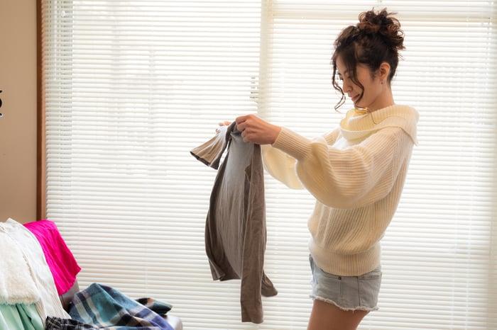 Une femme essayant des vêtements dans sa chambre