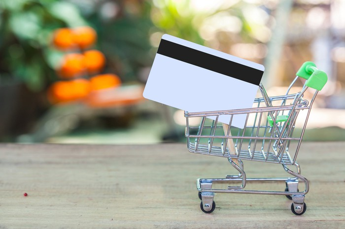 A credit card in a tiny shopping cart.