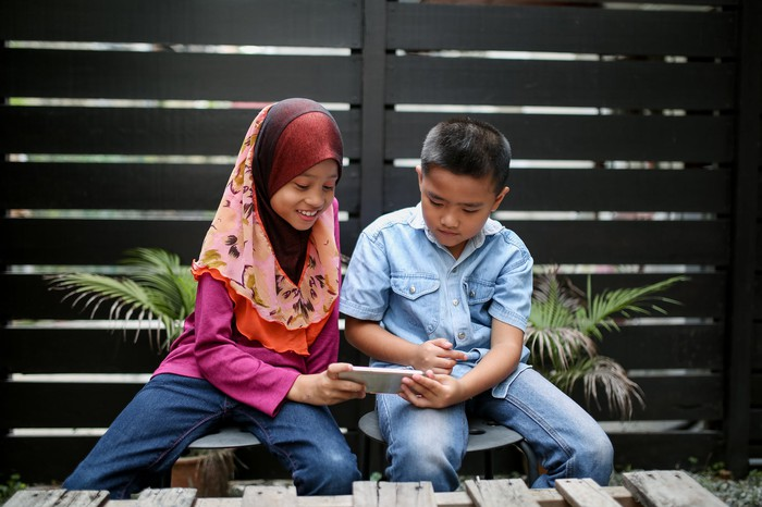 Two kids are playing on a phone.