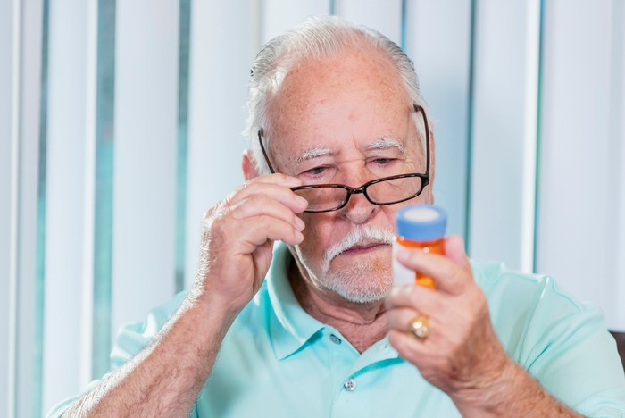 Gray-haired person adjusts eyeglasses while staring at pill bottle in hand