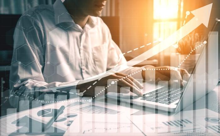 Une personne devant un ordinateur avec des graphiques financiers sur un bureau recouvert d'une flèche pointant vers le haut.