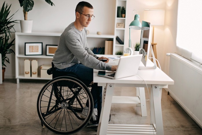 A young man in a wheelchair working on laptop at a desk.