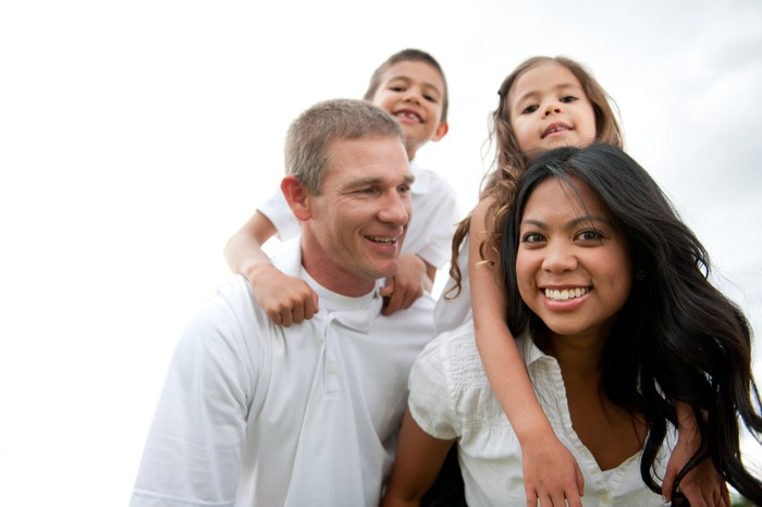 A family of four enjoying the outdoors, with both kids riding piggyback on their parents' shoulders.