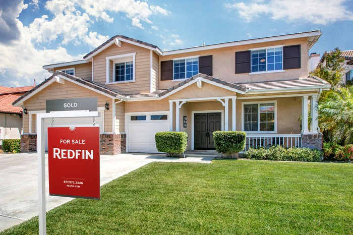 A Redfin for sale sign on the lawn in front of a two-story residence.