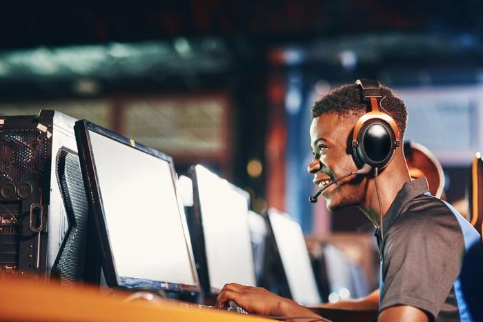 Person wearing headphones looking at computer screen.