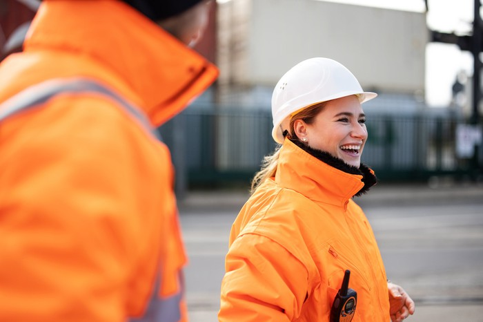 A person in a hardhat at an industrial complex.