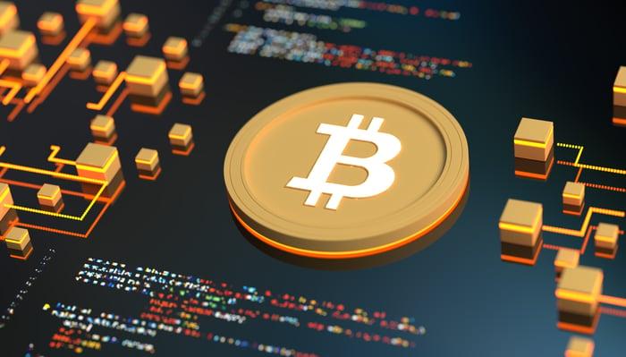 Gold bitcoin token on a circuit board.