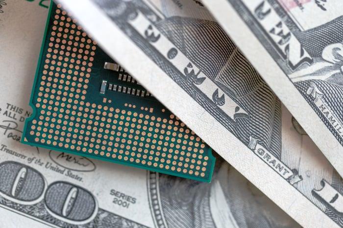 A desktop CPU peeks out from a bundle of various high-value dollar bills.
