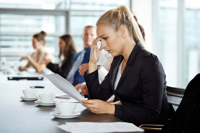 A business woman looking concerned as she looks at a document.