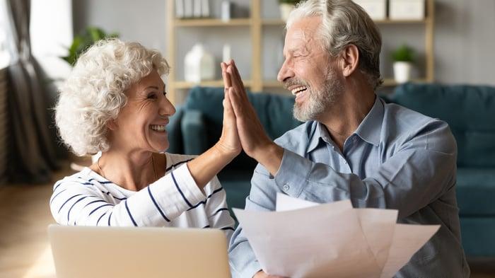 Un couple de personnes âgées qui donne cinq en regardant des papiers.