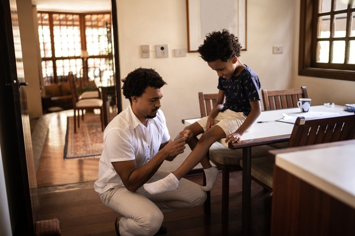 Homme soignant une blessure à la jambe d'un enfant.
