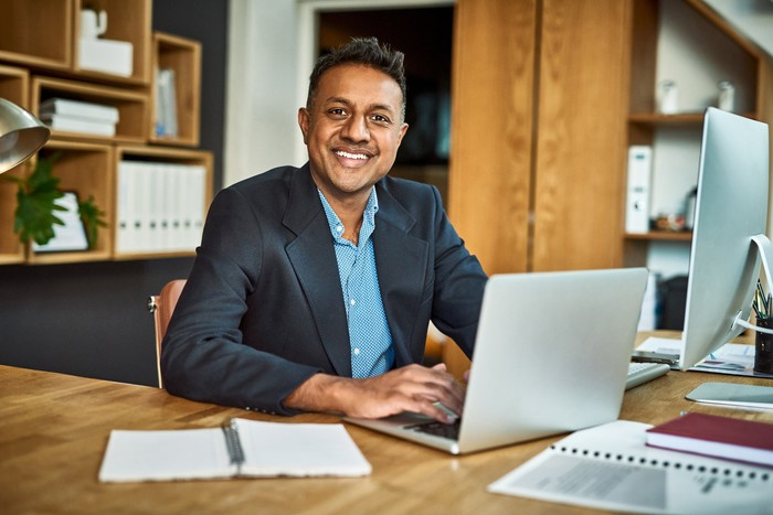 Smiling person in business suit at laptop.