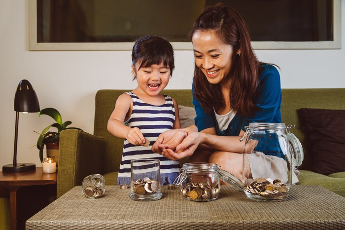 parent and child placing coins in savings jars