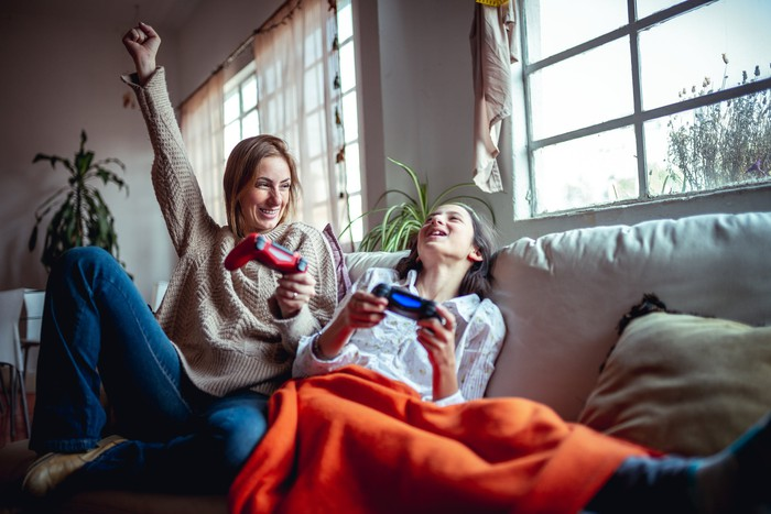 Mother and daughter on couch playing a video game.