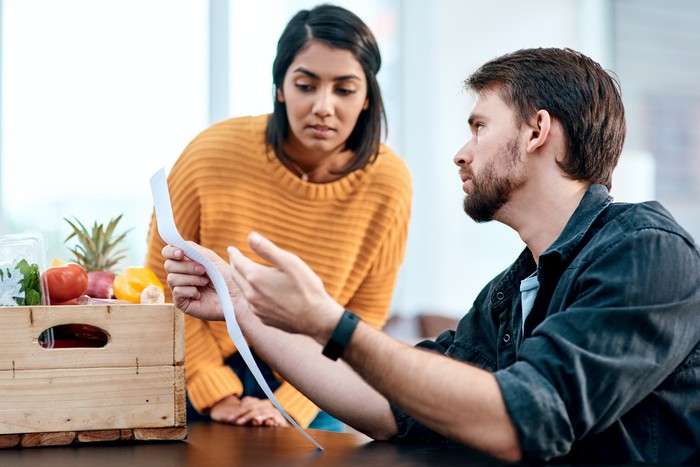 Two people with grocery box looking at receipt.