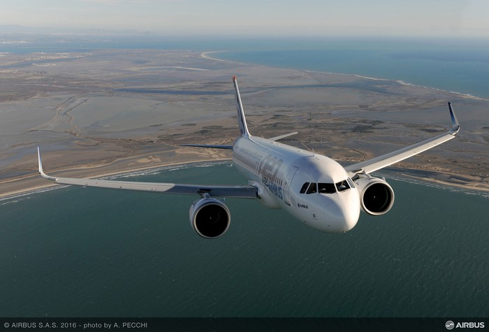 A frontal view of an Airbus A320neo flying over the water.
