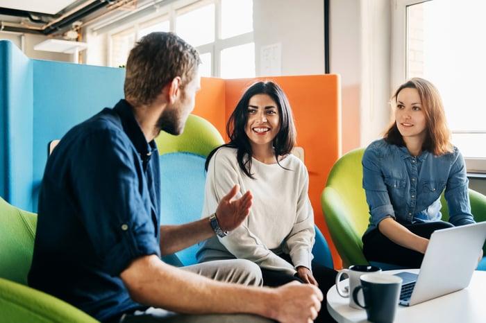 Les employés de bureau tenant une réunion sur la zone de conférence colorée avec des chaises de couleur vive