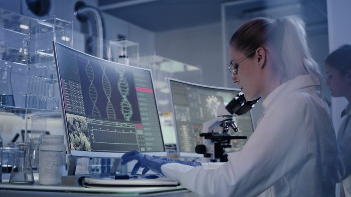 A researcher sitting at a computer screen with the DNA double-helix displayed.