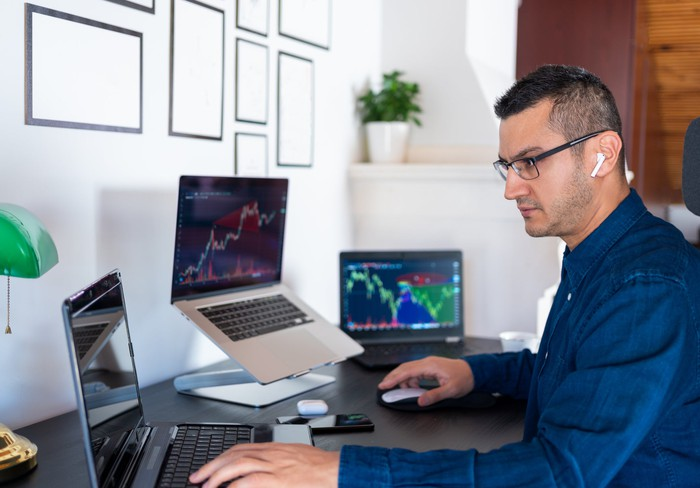 A worker studies crypto charts on multiple laptops in an office.