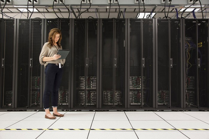 A woman standing in front of computer servers.