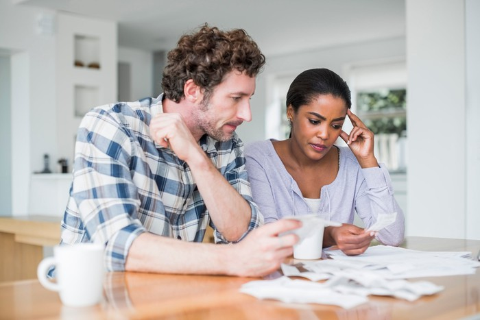 A worried couple sits at the kitchen table while examining a pile of papers.