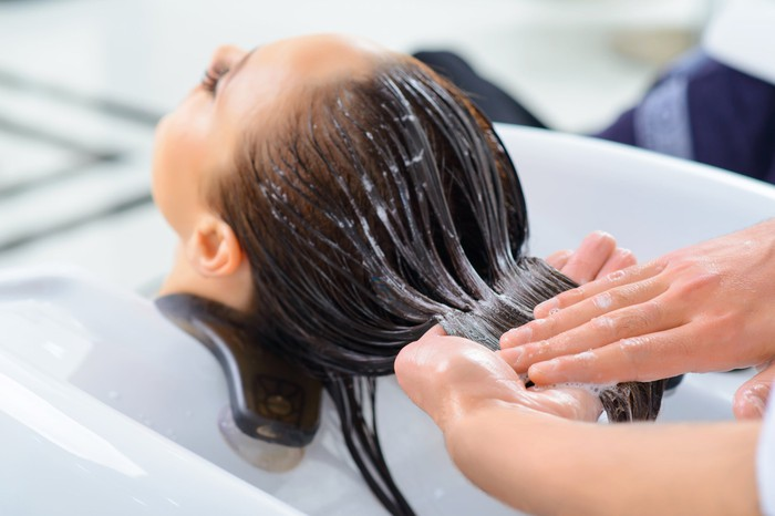 A person getting their hair washed at a salon.