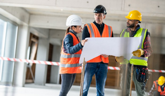 three workers in hard hats looking over a blueprint at a construction site