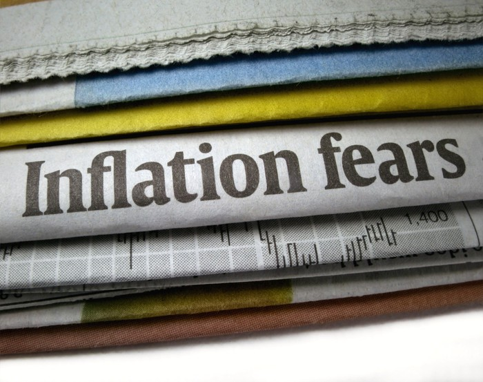 stack of newspapers with headline of inflation fears showing.