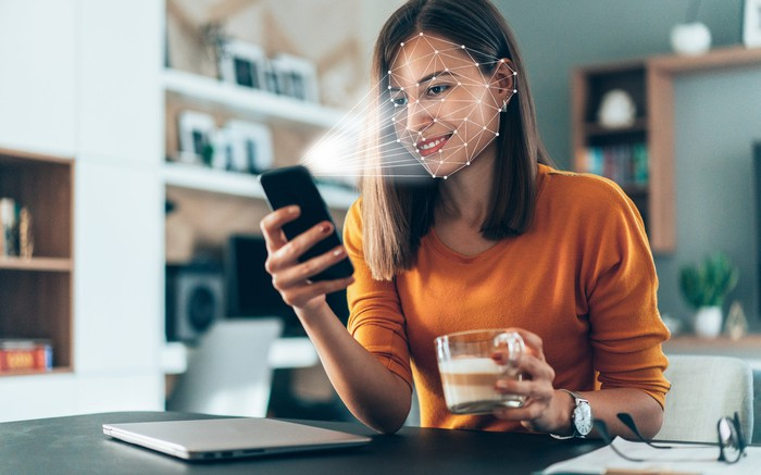 Young woman looks at smartphone in her home and the phone 3D senses her face.