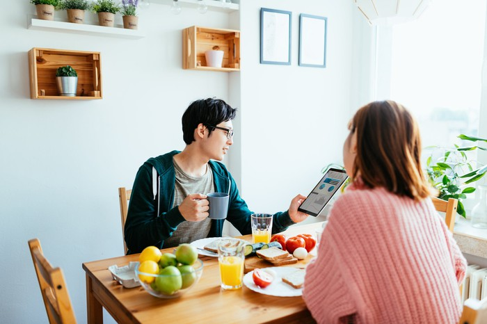 Two people sit at the breakfast table and look at a tablet.