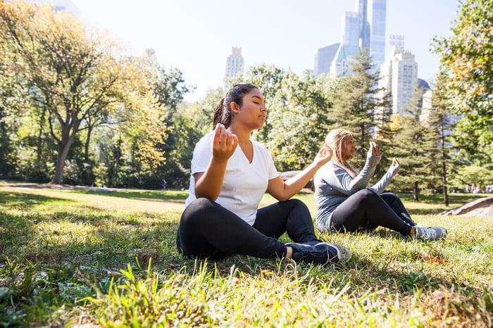 Deux personnes dans une pose de yoga dans une pelouse de parc avec skyline derrière.