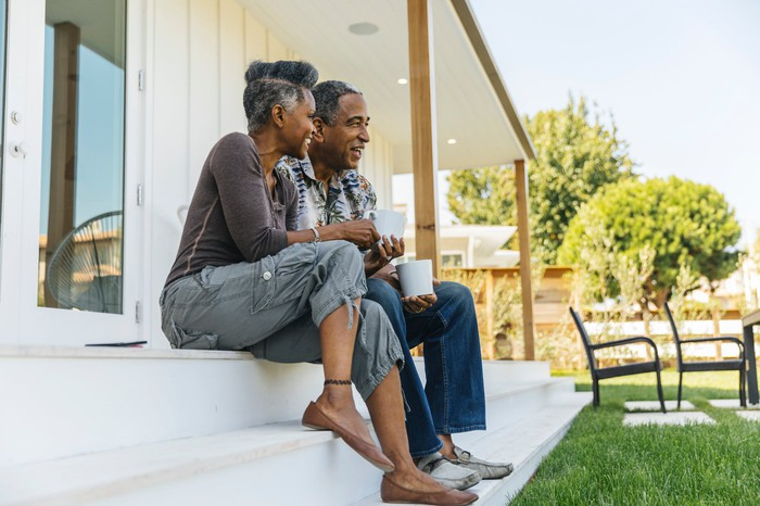 A couple sitting on their porch looking out over a nicely manicured lawn.